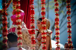 Indian Bride smiling with her groom in the backdrop of flowers hanging.