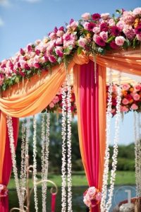 Cylindrical shaped floral decor in a backdrop of orange flowers set by experienced wedding managment company named Kiyoh