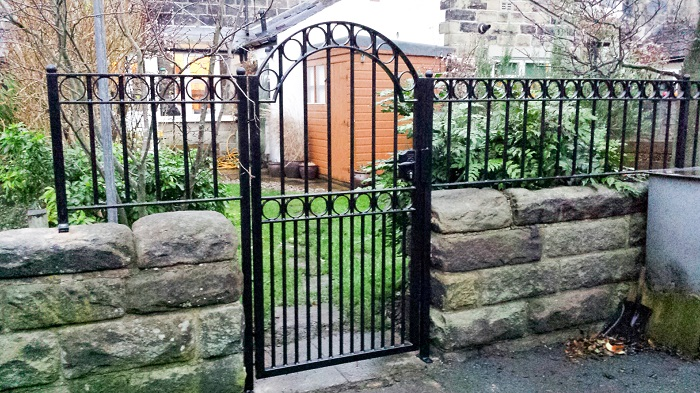 A short and small metal gate with rocky stone walls for a backyard garden.