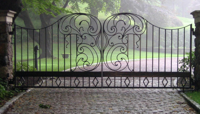 Ornamental metal driveway gates in a tranquil green environment.